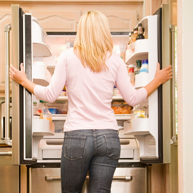 woman-standing-in-front-of-refrigerator-in-kitchen-picture-id520410157